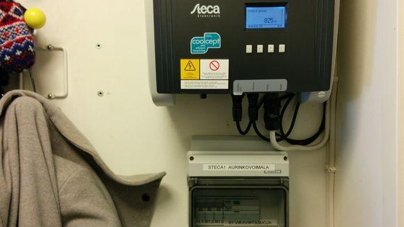 Kuvassa aurinkosähköjärjestelmän invertteri, joka muun muassa mittaa sisään tulevan energian määrän. Näytössä lukee 825w.