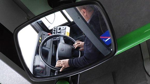 Kuljettaja linja-auton ratissa.
