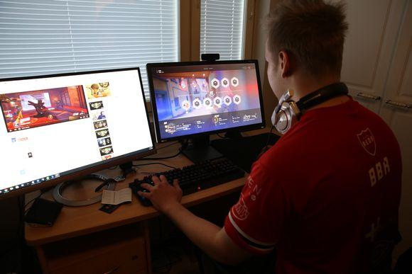 Mies pelaa tietokonepeliä kädet näppäimistöllä ja katse ruudulla.