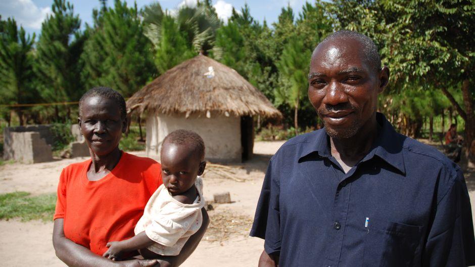 Ugandalainen Maxwell Oninje vaimonsa ja lapsensa kanssa.