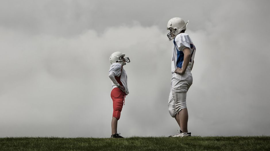 Pitkä ja lyhyt amerikkalaisen jalkapallon pelaaja vastakkain.