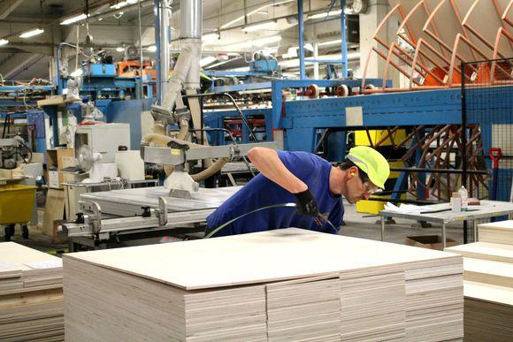 Työntekijä työstää vaneripinoa UPM Joensuun vaneritehtaalla