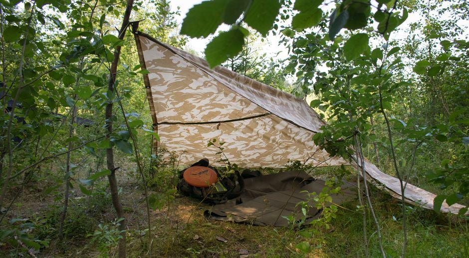 Laavu telttakankaasta kesällä metsässä.