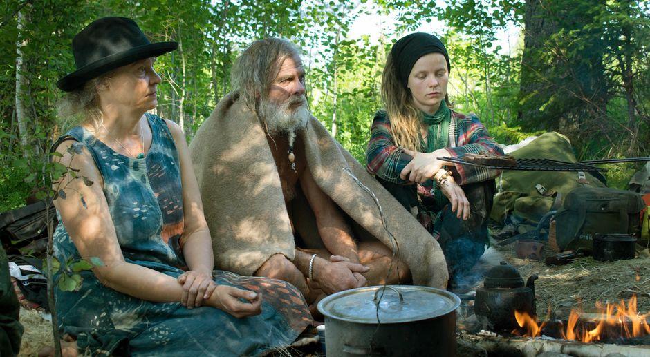 Ihmiset nuotion äärellä survivalistien leirillä Keski-Suomessa.