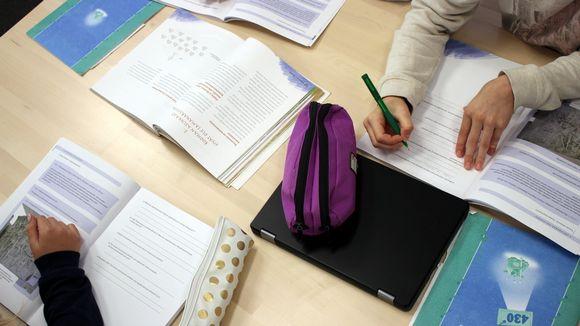 Oppilaat tekevät tehtäviä pöydän ääressä.