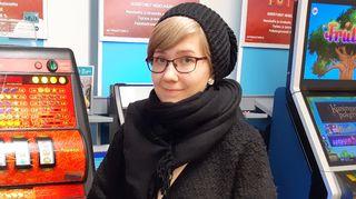 Nuori nainen seisoo kaupan rahapeliautomaattien edessä ja hymyilee.