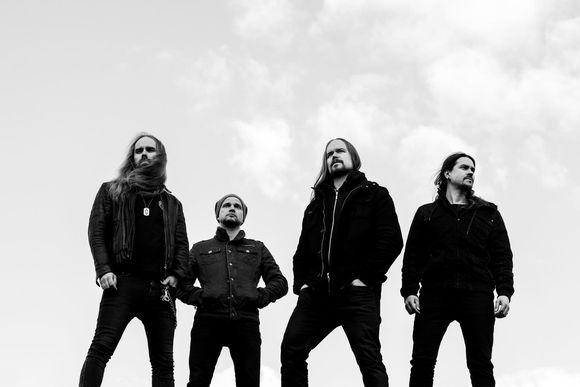 Insomniumin jäsenet seisovat rivissä tummissa vaatteissaan mustavalkoisessa kuvassa taivas takanaan.