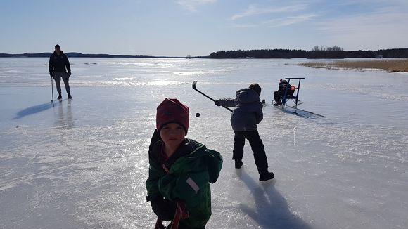 Lapset pelaavat jääkiekkoa järven jäällä