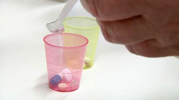 Hoitaja annostelee lääkkeitä pieniin lääkemukeihin.