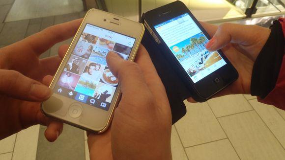 Kaksi henkilöä näppäilee puhelimissaan käytössä olevia facebook- ja instagram-sovelluksia.