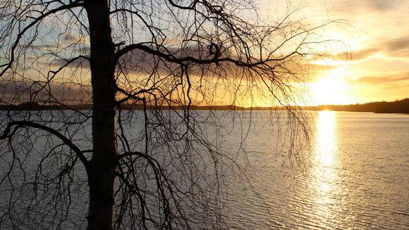 Aurinko nousee Rahkeenvedellä Joensuun Uimaharjussa.