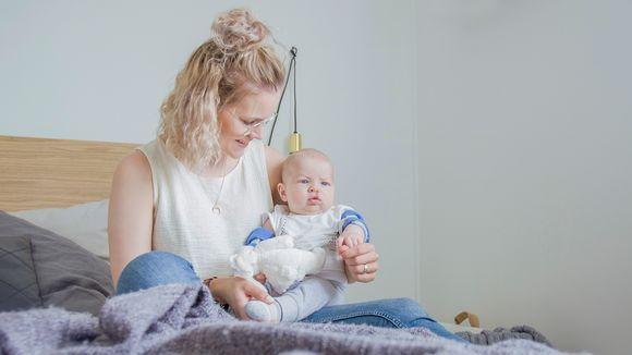 Äiti istuu poikansa kanssa sängyllä