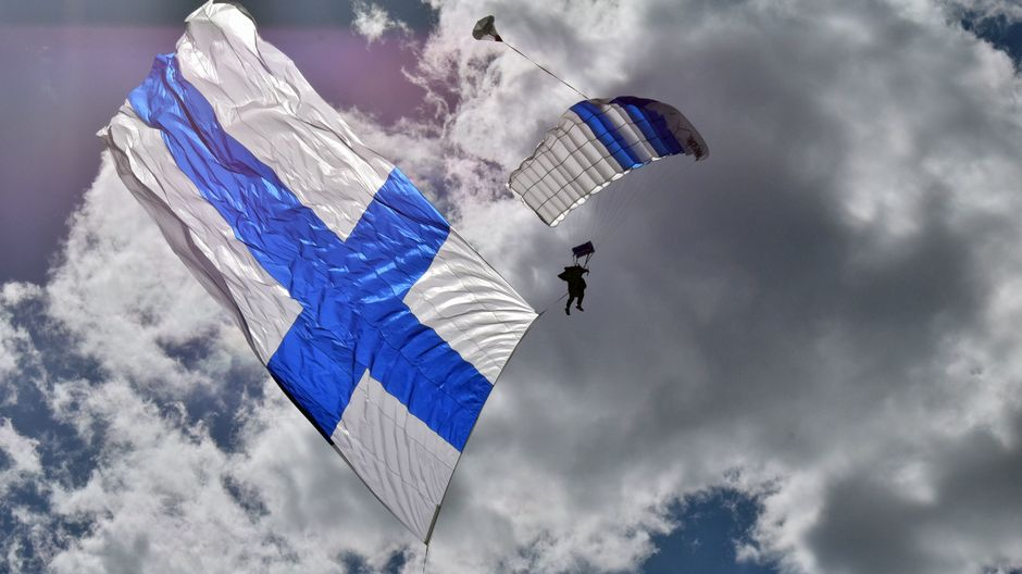Laskuvarjohyppääjä ja iso Suomen lippu.