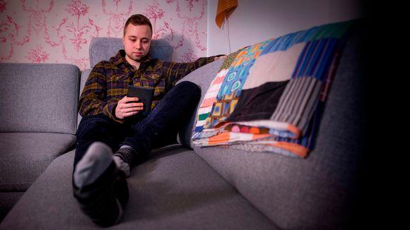 Mika Hartio lukee e-kirjaa sohvalla