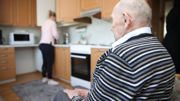 Lähihoitaja tiskaa kotona, 95 vuotias veteraani istuu keittiössä.