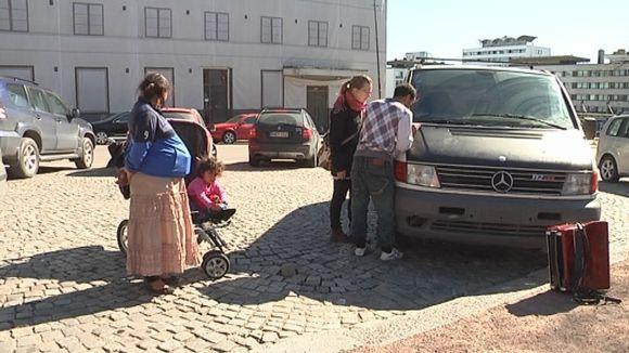 Romanikerjäläisperhe pakettiautonsa vieressä.