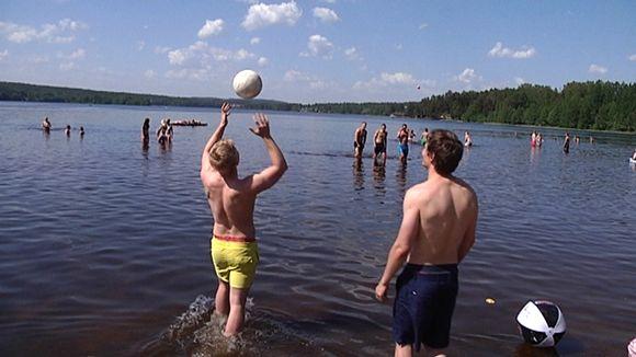 Pojat kahlaavat vedessä