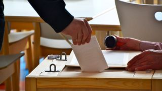 Äänestyslappu pudotetaan uurnaan.