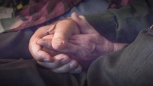 Vanhukset istuvat sohvalla, lähikuva käsistä.