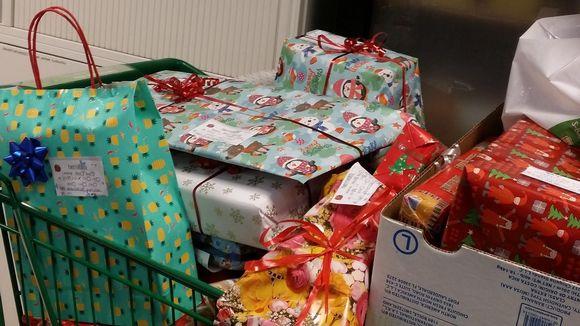 Paketoituja joululahjoja ostoskärryissä.