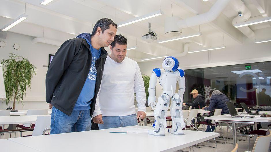 Kaksi miestä keskustelee humanoidorobotin kanssa.