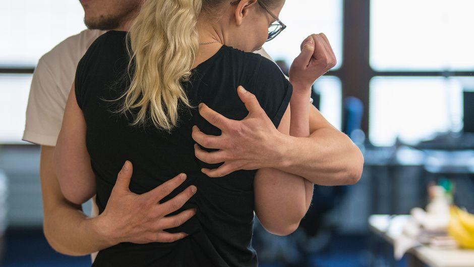 Mies halaa naista, joka ei halua tulla halatuksi.