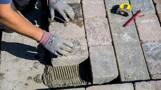 Työntekijän kädet tekemässä katukivetystä.