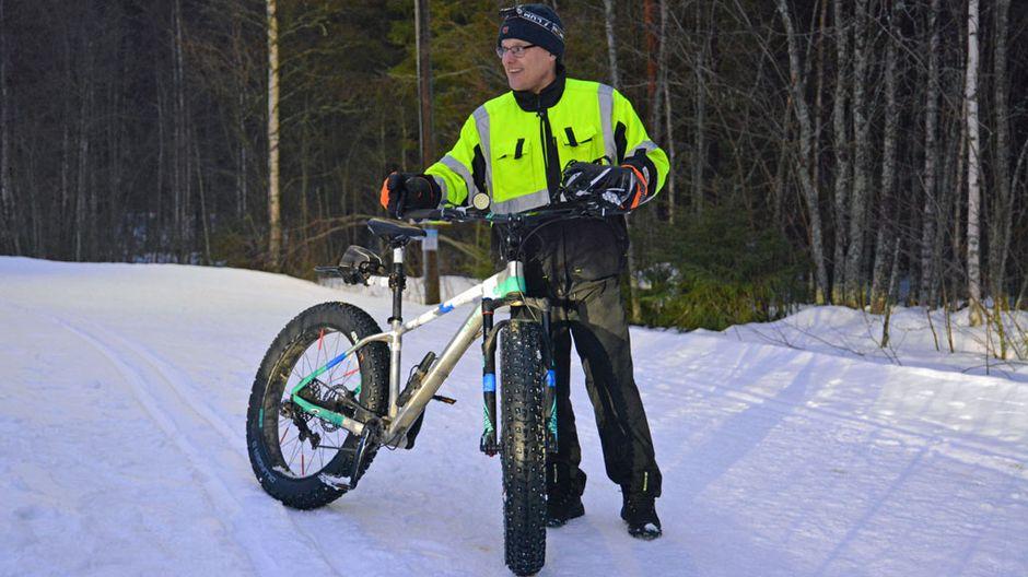 Mies näyttää, miten pieni jälki ladulle jää läskipyörän renkaasta.