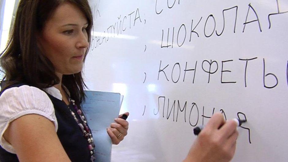 Opettaja kirjoittaa tussilla taululle kyyrillisiä kirjaimia