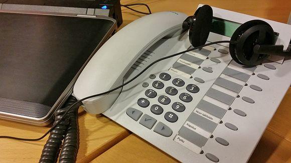 Puhelin läppärin vieressä kuulokkeiden alla.