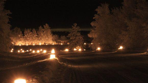 Luminen ja pimeä maisema, jossa jäälyhtyjä tien varrella