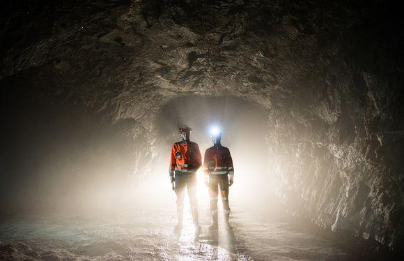 Kaksi kaivoksen työntekijää maanalaisessa tunnelissa.
