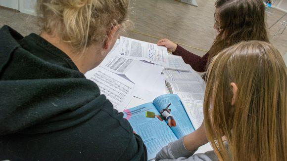 Opiskelijat selaavat opintomateriaalia pöydän ääressä.