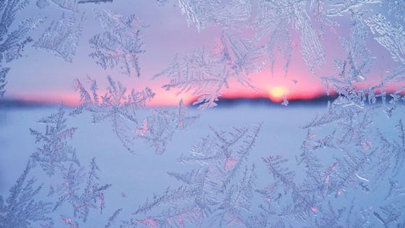 Jäähiutaleita ikkunassa ja takana auringonlasku.
