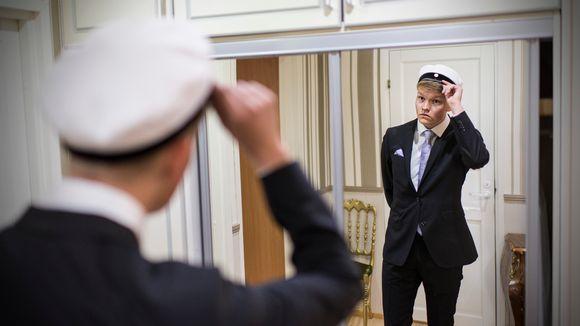 Aaro Åivo sovittaa ylioppilaslakkia päähänsä peilin edessä.