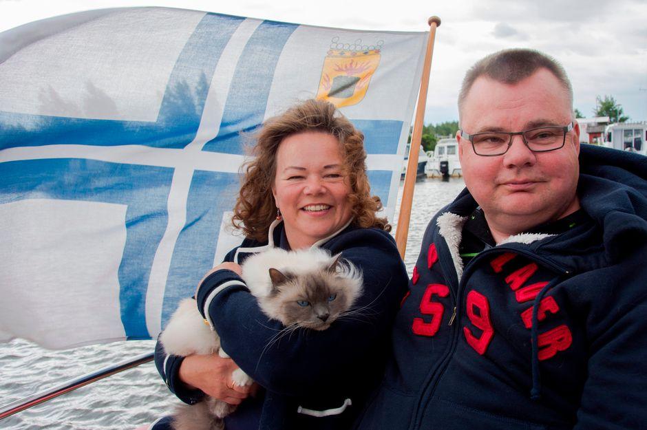 Päivi Kant-Bergroth ja Mikael Bergroth istuvat kissansa Jussin kanssa tuulisen veneen kannella.