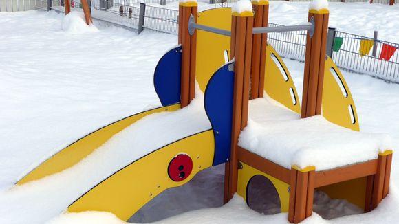 Kuvassa lasten liukumäki päiväkodin lumisella pihalla.