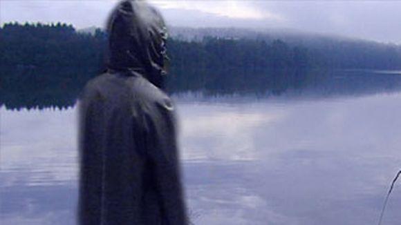 Hahmo seisoo järven rannalla.