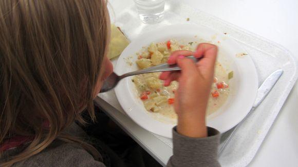 Kuvassa lapsi lusikoi suuhun keittoruokaa