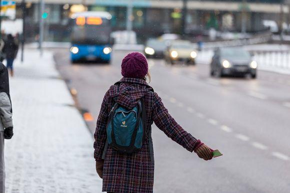Ihmiset näyttävät pysäyttämismerkki tuleville busseille.