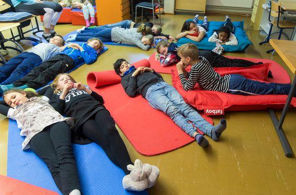 Lapset nukkuvat koulun lattialla.