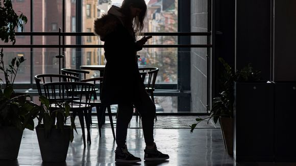 Nuori selailee kännykkää, silhuetti.