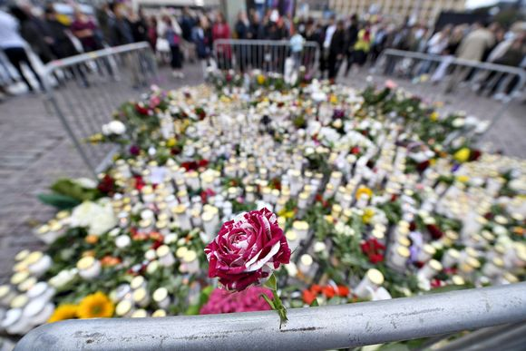 Surijat ovat tuoneet muistokynttilöitä ja kukkia Turun perjantaisen puukotusiskun uhreille Turun kauppatorille lauantaina 19. elokuuta 2017.