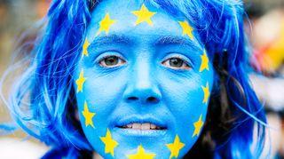 Eu:n lippu maalattuna nuoren naisen kasvoihin.