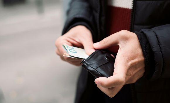 Mies pitelee lompakkoa
