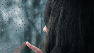 Audio: Naine katselee sateisen ikkunan läpi.