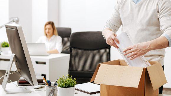Mies pakkaa tavaroitaan työpaikalla.