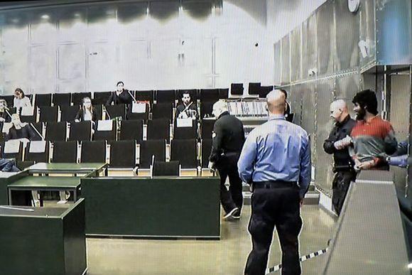 Vartijat tuovat Turun elokuisen puukkoiskun tekijän Abderrahman Bouananen Turun vankilan saliin.