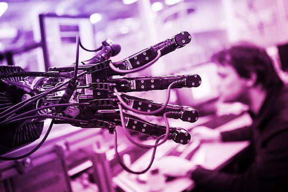 Mies tietokoneen ääressä ja etualalla kuvaa robottikäsi