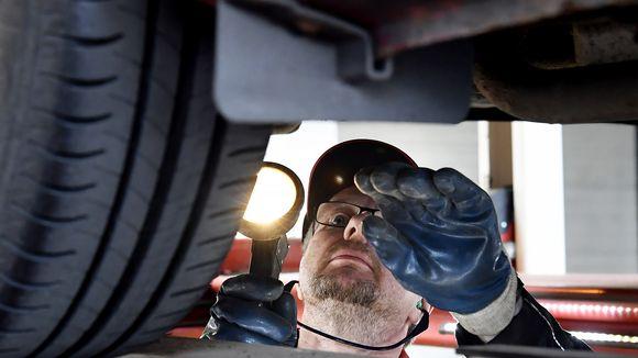 Katsastaja tarkistaa auton pohjan.